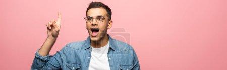 Photo pour Un homme excité a des idées et regarde loin isolé sur une photo panoramique rose - image libre de droit