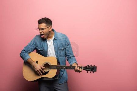 Photo pour Jeune homme qui sort la langue en jouant à la guitare acoustique sur fond rose - image libre de droit
