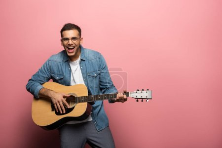 Photo for Young laughing man looking at camera while playing on acoustic guitar on pink background - Royalty Free Image