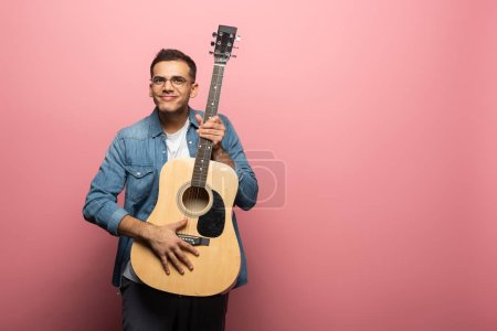 Photo for Man smiling at camera and holding acoustic guitar on pink background - Royalty Free Image