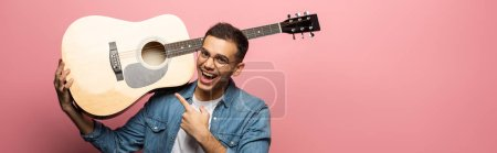 Photo for Panoramic shot of cheerful man pointing on acoustic guitar on pink background - Royalty Free Image