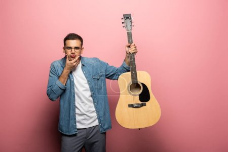 Photo for Handsome man grimacing at camera and holding acoustic guitar on pink background - Royalty Free Image