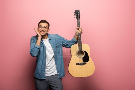 Photo for Young smiling man grimacing while holding acoustic guitar on pink background - Royalty Free Image