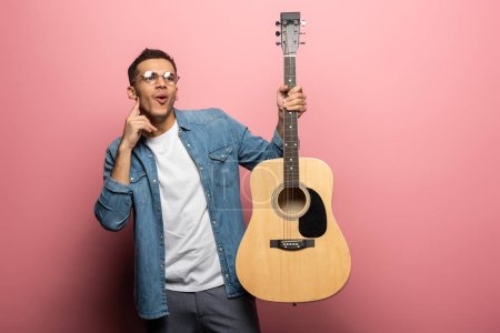 Photo for Shocked man with finger by cheek holding acoustic guitar on pink background - Royalty Free Image