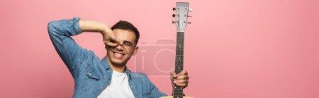 Photo pour Prise de vue panoramique d'un homme souriant avec geste de guitare acoustique isolé sur rose - image libre de droit
