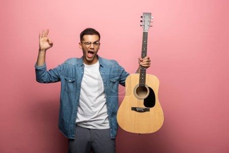 Photo for Man with acoustic guitar winking and showing okay sign on pink background - Royalty Free Image