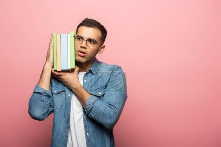Photo pour Jeune homme pensif tenant des livres sur fond rose avec espace de copie - image libre de droit