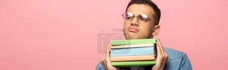 Photo pour Homme sceptique avec des livres regardant loin isolé sur rose, plan panoramique - image libre de droit