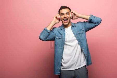Photo pour Jeune homme positif dans les écouteurs regardant la caméra sur fond rose - image libre de droit
