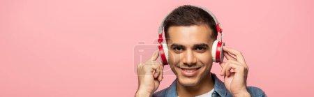 Photo pour Vue panoramique de l'homme dans les écouteurs souriant à la caméra isolée sur rose - image libre de droit