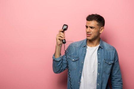 Foto de Hombre temeroso que mira al teléfono en el fondo rosa - Imagen libre de derechos