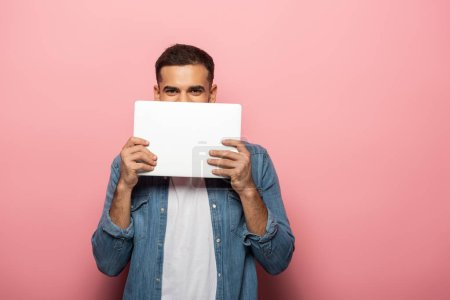 Young man covering face with laptop and looking at camera on pink background