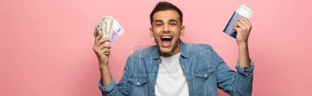 Photo pour Photo panoramique d'un homme excité en possession d'argent liquide, d'un passeport et d'une carte d'embarquement sur fond rose - image libre de droit