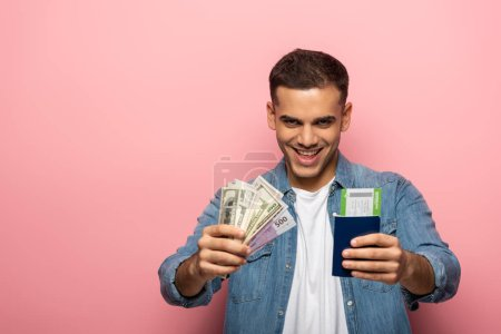 Man holding passport with boarding pass and cash while smiling at camera on pink background