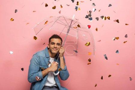 Photo pour Jeune homme portant un parapluie souriant à la caméra sous un confetti en forme de coeur tombant sur fond rose - image libre de droit