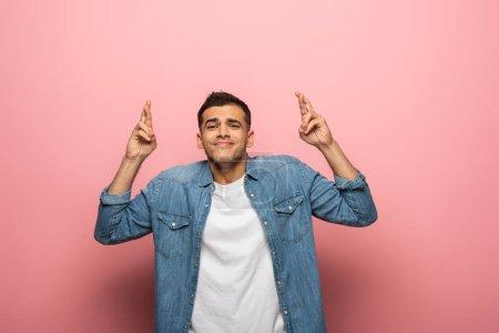 Photo pour Jeune homme aux doigts croisés souriant à la caméra sur fond rose - image libre de droit