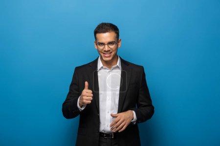 Foto de Un hombre de negocios sonriente que muestra un gesto de pulso sobre el fondo azul - Imagen libre de derechos