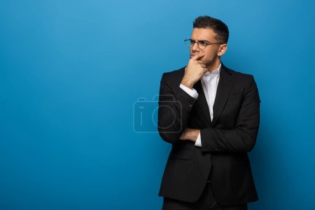 Foto de Thoughtful business man with hand by chin looking away on blue background. - Imagen libre de derechos