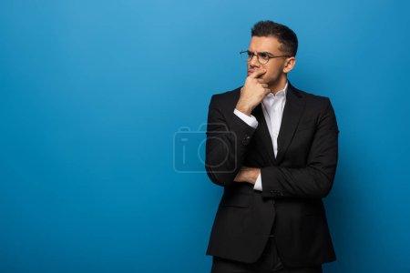Photo pour Homme d'affaires réfléchi avec la main par le menton regardant loin sur fond bleu - image libre de droit