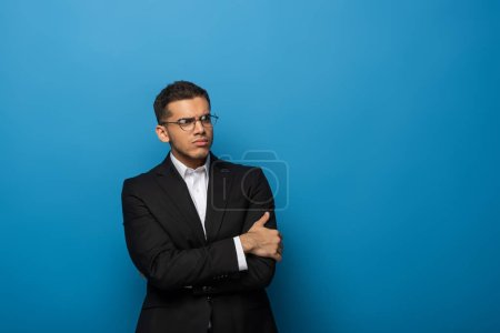 Sceptical businessman with crossed arms looking away on blue background