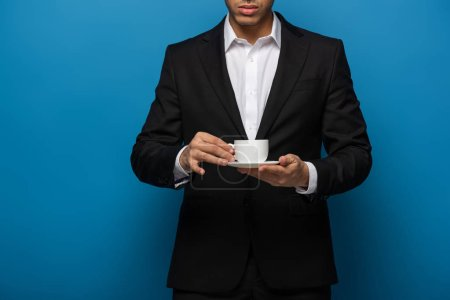 Cropped view of businessman holding coffee cup and saucer on blue background
