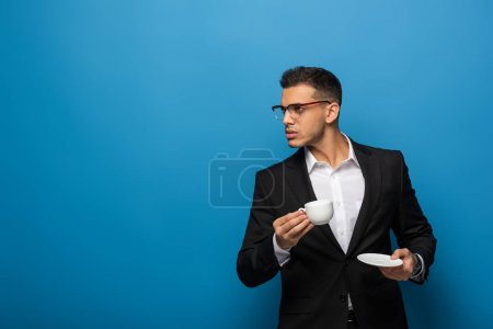 Handsome businessman with coffee cup looking away on blue background