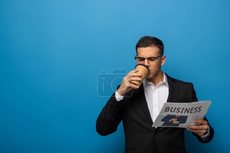 Photo for Handsome businessman with coffee to go reading newspaper on blue background - Royalty Free Image