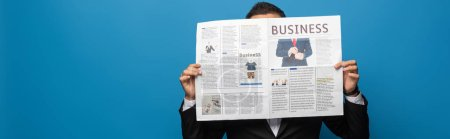 Photo for Panoramic shot of businessman covering face while reading newspaper isolated on blue - Royalty Free Image