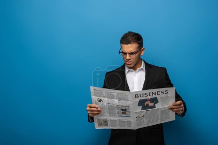 Photo for Thoughtful businessman reading newspaper on blue background - Royalty Free Image