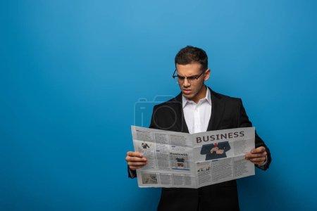 Photo pour Homme d'affaires réfléchi lecture journal sur fond bleu - image libre de droit