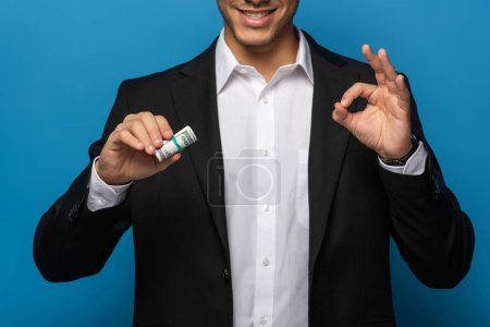 Photo for Cropped view of smiling businessman showing okay gesture and holding cash roll on blue background - Royalty Free Image