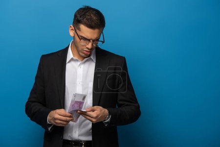 Photo for Young businessman counting euro banknotes on blue background - Royalty Free Image