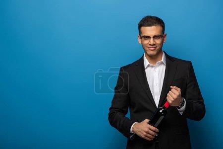 Handsome businessman holding bottle of wine and smiling at camera on blue background