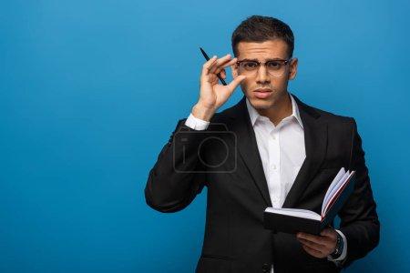 Handsome businessman with pen and notebook adjusting eyeglasses on blue background