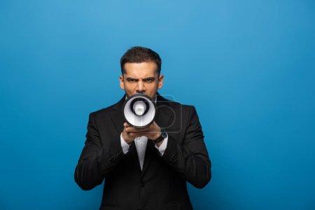 Photo pour Homme d'affaires criant dans haut-parleur et regardant la caméra sur fond bleu - image libre de droit