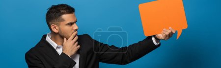 Photo for Panoramic shot of pensive businessman looking at speech bubble on blue background - Royalty Free Image