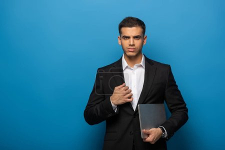 Handsome businessman with laptop looking at camera on blue background