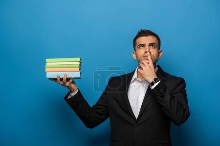 Photo pour Homme d'affaires réfléchi avec la main sur la bouche tenant des livres sur fond bleu - image libre de droit