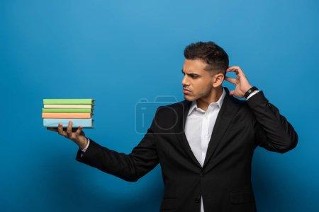 Photo pour Homme d'affaires pensif regardant des livres colorés sur fond bleu - image libre de droit