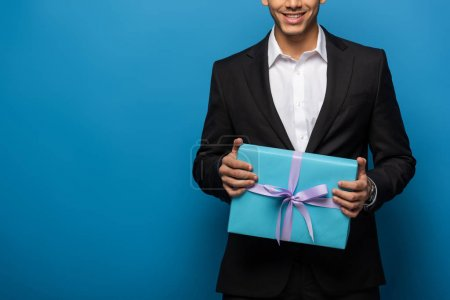 Photo for Cropped view of smiling businessman with gift on blue background - Royalty Free Image
