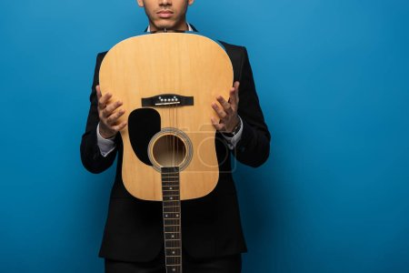 Photo for Cropped view of businessman holding acoustic guitar on blue background - Royalty Free Image