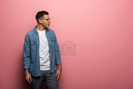 Photo pour Vue latérale de l'homme choqué regardant loin sur fond rose - image libre de droit