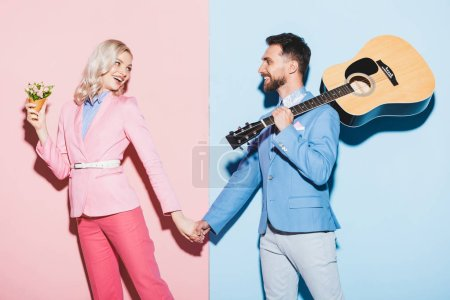 Photo for Smiling woman with bouquet and handsome man with acoustic guitar holding hands on pink and blue background - Royalty Free Image
