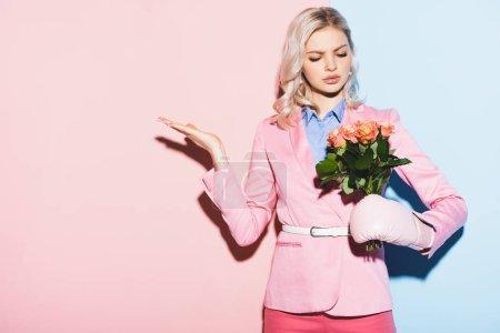 Photo pour Femme triste en gant de boxe tenant bouquet sur fond rose et bleu - image libre de droit