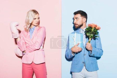 Photo pour Femme sérieuse avec des gants de boxe et homme effrayé avec cadeau et bouquet sur fond rose et bleu - image libre de droit