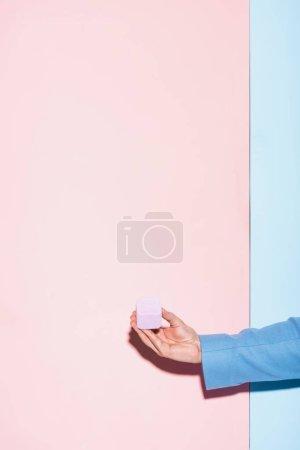 Photo pour Vue recadrée de l'homme tenant boîte sur fond bleu et rose - image libre de droit