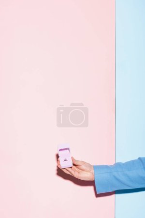 cropped view of man holding box with engagement ring on blue and pink background