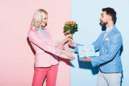 schöner Mann schenkt lächelnden Frau Strauß und Geschenk auf rosa und blauem Hintergrund