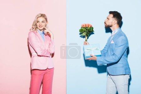 schöner Mann schenkt verträumten Frau Strauß und Geschenk auf rosa und blauem Hintergrund