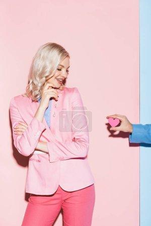 Photo pour Vue recadrée de l'homme donnant carte en forme de coeur à la femme souriante sur fond rose et bleu - image libre de droit